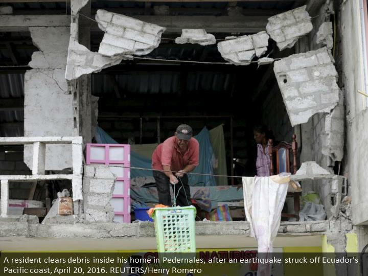 A resident clears debris inside his home in Pedernales, after an earthquake struck off Ecuador's Pacific coast, April 20, 2016. REUTERS/Henry Romero