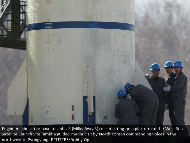 Engineers check the base of Unha-3 (Milky Way 3) rocket sitting on a launch pad at the West Sea Satellite Launch Site, during a guided media tour by North Korean authorities in the northwest of Pyongyang. REUTERS/Bobby Yip