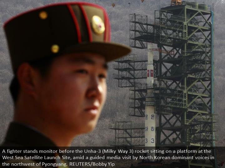A soldier stands guard in front of the Unha-3 (Milky Way 3) rocket sitting on a launch pad at the West Sea Satellite Launch Site, during a guided media tour by North Korean authorities in the northwest of Pyongyang. REUTERS/Bobby Yip
