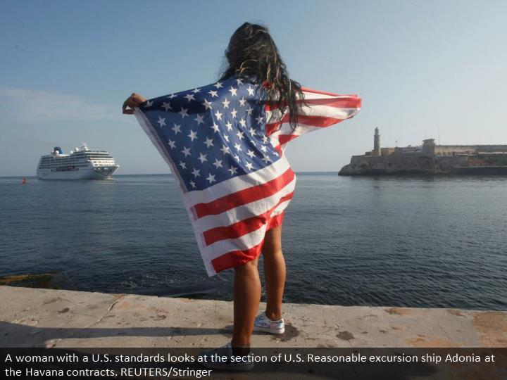 A woman with a U.S. flags looks at the arrival of U.S. Carnival cruise ship Adonia at the Havana bay. REUTERS/Stringer