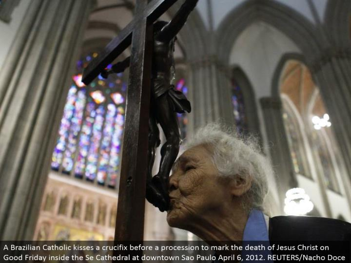 A Brazilian Catholic kisses a cross before a parade to check the demise of Jesus Christ on Good Friday inside the Se Cathedral at downtown Sao Paulo April 6, 2012. REUTERS/Nacho Doce