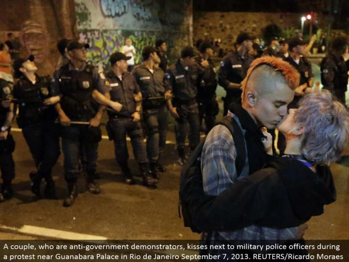 A couple, who are hostile to government demonstrators, kisses by military cops amid a challenge close Guanabara Palace in Rio de Janeiro September 7, 2013. REUTERS/Ricardo Moraes