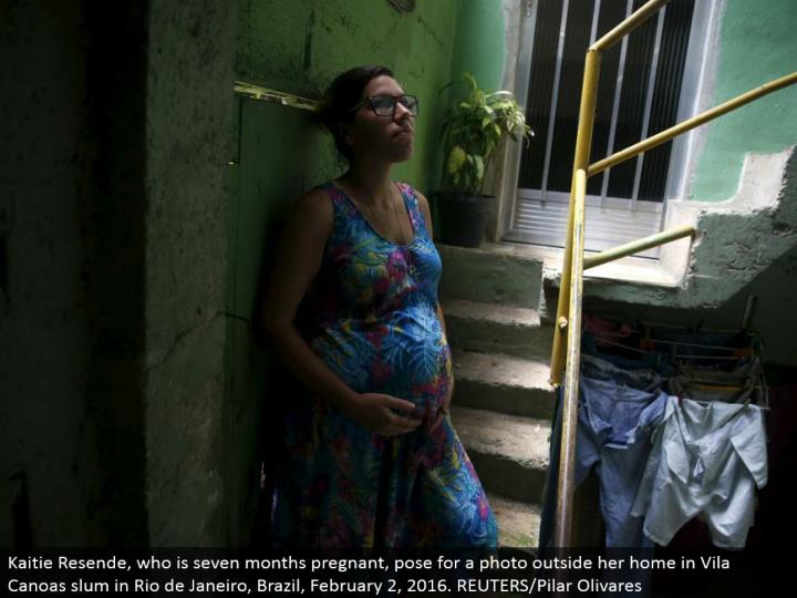 Kaitie Resende, who is seven months pregnant, posture for a photograph outside her home in Vila Canoas ghetto in Rio de Janeiro, Brazil, February 2, 2016. REUTERS/Pilar Olivares