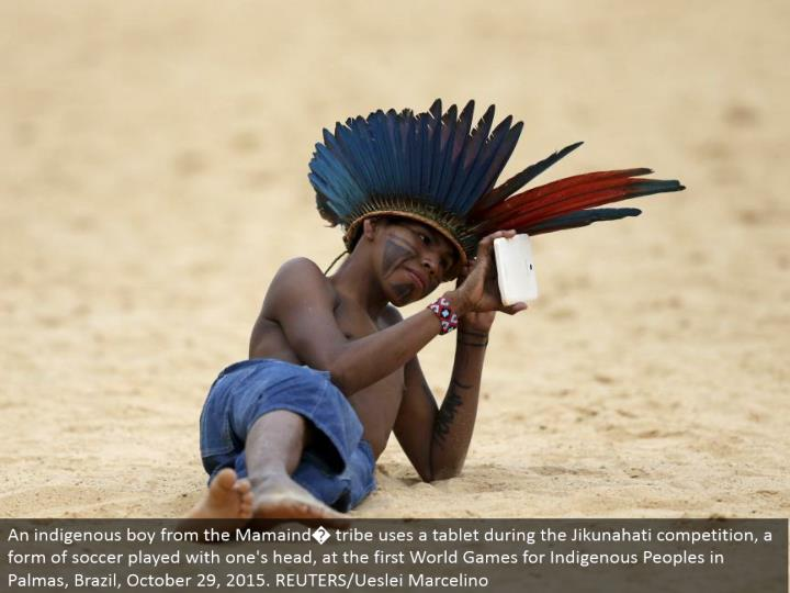 An indigenous kid from the Mamaind� tribe utilizes a tablet amid the Jikunahati rivalry, a type of soccer played with one's head, at the main World Games for Indigenous Peoples in Palmas, Brazil, October 29, 2015. REUTERS/Ueslei Marcelino