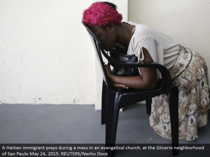 A Haitian settler supplicates amid a mass in a zealous church, at the Glicerio neighborhood of Sao Paulo May 24, 2015. REUTERS/Nacho Doce