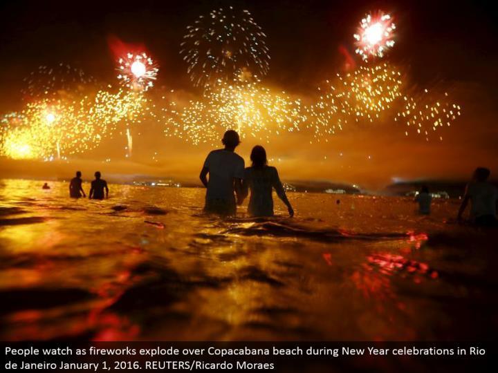 People look as firecrackers blast over Copacabana shoreline amid New Year festivities in Rio de Janeiro January 1, 2016. REUTERS/Ricardo Moraes