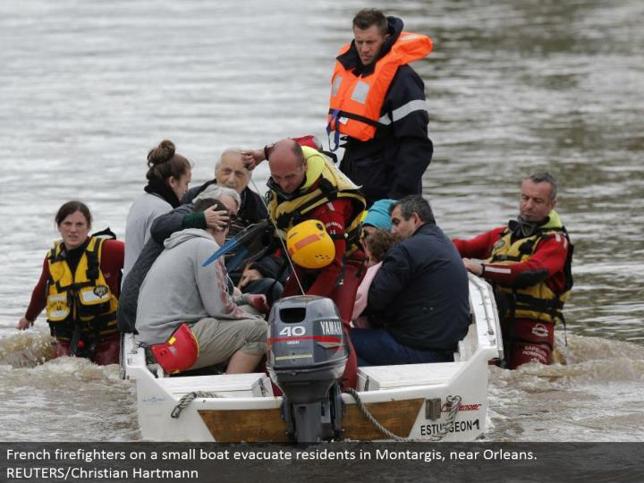 French firefighters on a little watercraft clear inhabitants in Montargis, close Orleans. REUTERS/Christian Hartmann