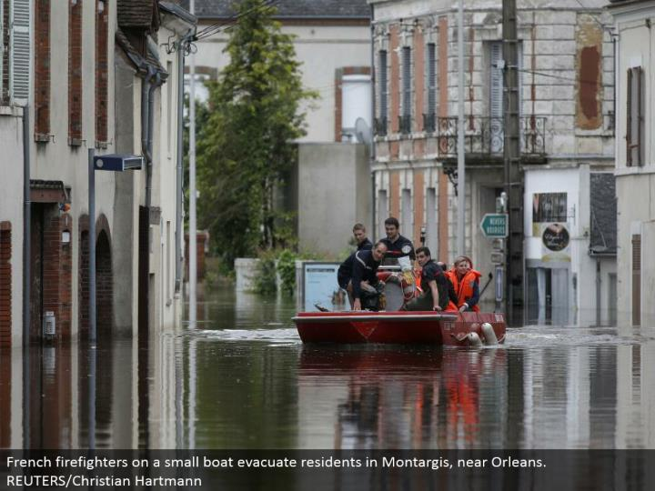 French firefighters on a little vessel empty inhabitants in Montargis, close Orleans. REUTERS/Christian Hartmann