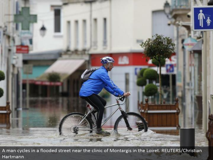 A man cycles in an overwhelmed road close to the center of Montargis in the Loiret. REUTERS/Christian Hartmann