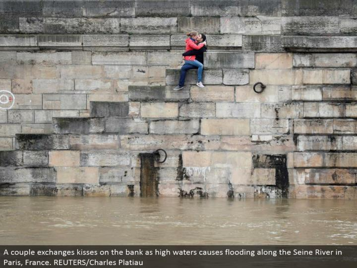 A couple trades kisses on the bank as high waters causes flooding along the Seine River in Paris, Fr...