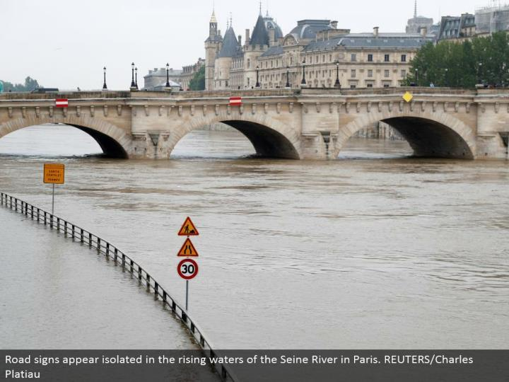 Road signs seem disconnected in the rising waters of the Seine River in Paris. REUTERS/Charles Platiau