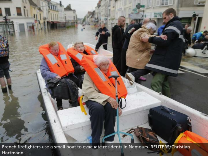 French firefighters utilize a little vessel to clear occupants in Nemours. REUTERS/Christian Hartman...