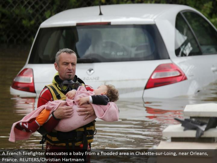 A French firefighter clears an infant from an overwhelmed territory in Chalette-sur-Loing, close Orleans, France. REUTERS/Christian Hartmann