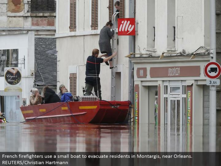 French firefighters utilize a little vessel to clear occupants in Montargis, close Orleans. REUTERS/Christian Hartmann