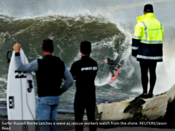 Surfer Russell Bierke gets a wave as salvage laborers watch from the shore. REUTERS/Jason Reed