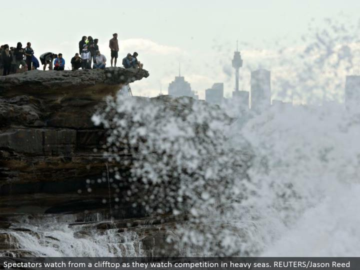 Spectators watch from a clifftop as they watch rivalry in overwhelming oceans. REUTERS/Jason Reed