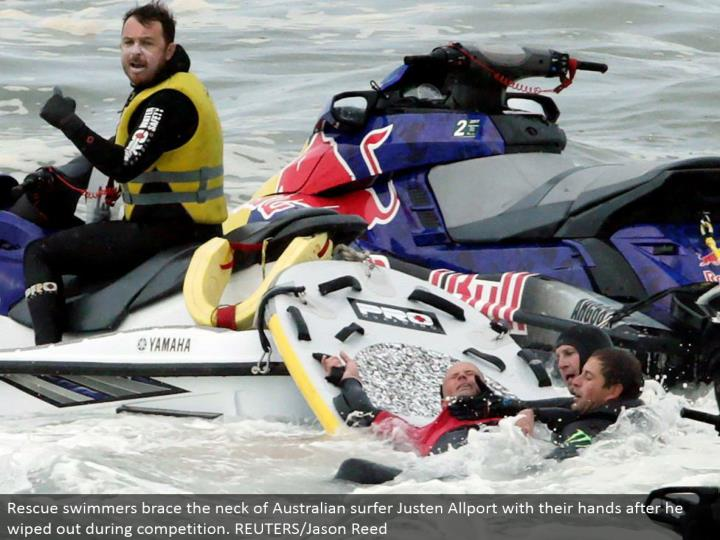 Rescue swimmers prop the neck of Australian surfer Justen Allport with their hands after he wiped out amid rivalry. REUTERS/Jason Reed