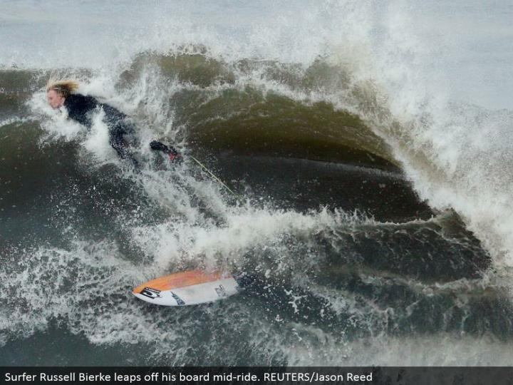 Surfer Russell Bierke jumps off his board mid-ride. REUTERS/Jason Reed