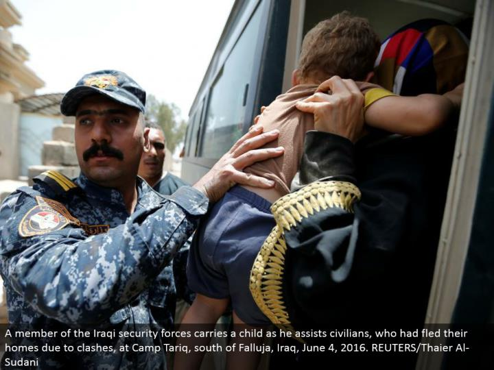 A individual from the Iraqi security powers conveys a tyke as he helps regular people, who had fled their homes because of conflicts, at Camp Tariq, south of Falluja, Iraq, June 4, 2016. REUTERS/Thaier Al-Sudani