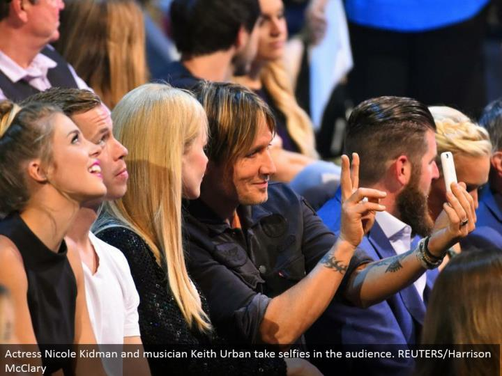 Actress Nicole Kidman and artist Keith Urban take selfies in the group of onlookers. REUTERS/Harrison McClary