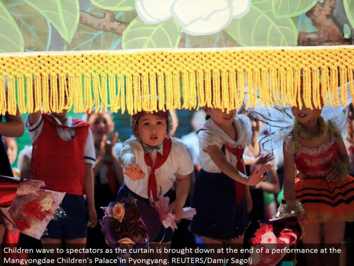 Children wave to onlookers as the window ornament is brought down toward the end of an execution at the Mangyongdae Children's Palace in Pyongyang. REUTERS/Damir Sagolj