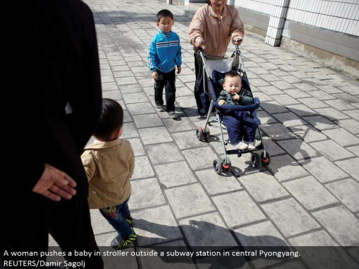 A lady pushes an infant in stroller outside a tram station in focal Pyongyang. REUTERS/Damir Sagolj
