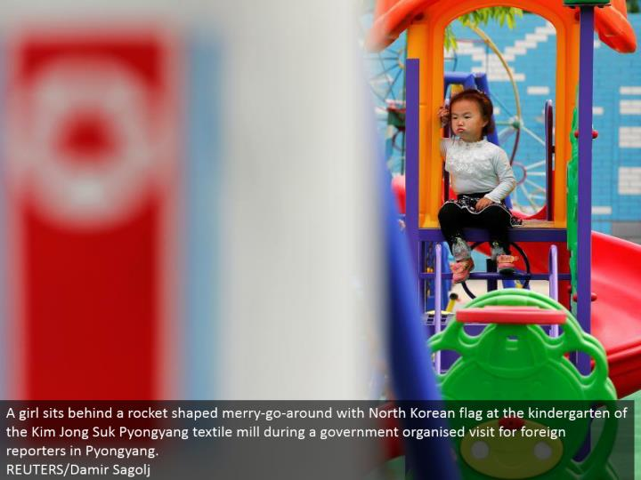A young lady sits behind a rocket formed happy run around with North Korean banner at the kindergarten of the Kim Jong Suk Pyongyang material factory amid an administration sorted out visit for outside journalists in Pyongyang.  REUTERS/Damir Sagolj