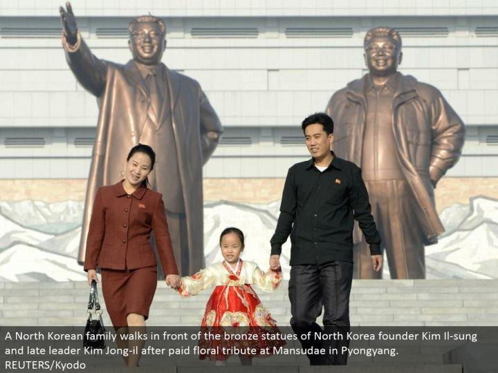 A North Korean family strolls before the bronze statues of North Korea originator Kim Il-sung and late pioneer Kim Jong-il after paid botanical tribute at Mansudae in Pyongyang.  REUTERS/Kyodo
