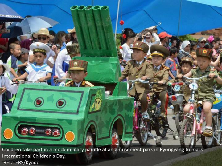 Children join in a fake military parade at a carnival in Pyongyang to stamp International Children's Day.  REUTERS/Kyodo
