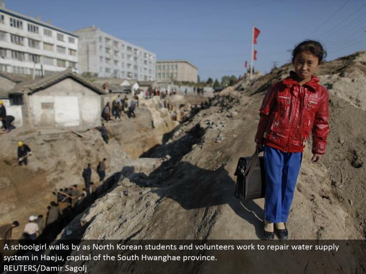 A schoolgirl strolls by as North Korean understudies and volunteers work to repair water supply framework in Haeju, capital of the South Hwanghae territory.  REUTERS/Damir Sagolj