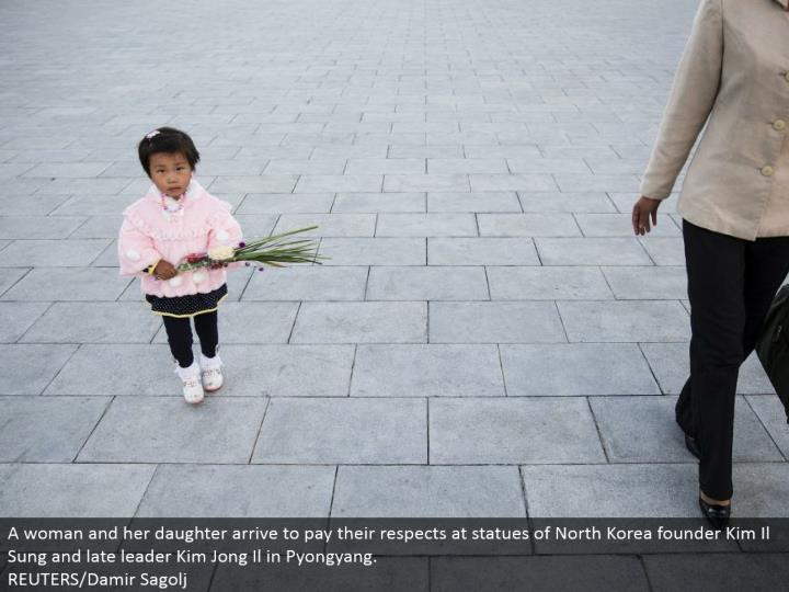 A lady and her little girl touch base to offer their regards at statues of North Korea organizer Kim Il Sung and late pioneer Kim Jong Il in Pyongyang.  REUTERS/Damir Sagolj