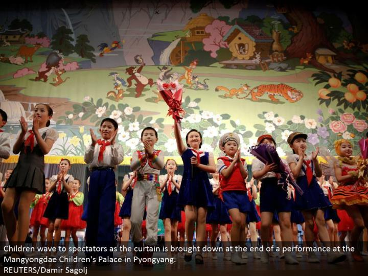Children wave to observers as the window ornament is brought down toward the end of an execution at the Mangyongdae Children's Palace in Pyongyang.  REUTERS/Damir Sagolj