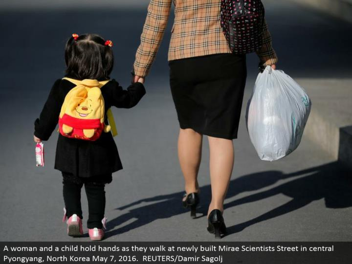 A lady and a youngster clasp hands as they stroll at recently fabricated Mirae Scientists Street in focal Pyongyang, North Korea May 7, 2016. REUTERS/Damir Sagolj
