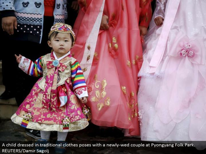 A youngster wearing customary dresses postures with a recently marry couple at Pyongyang Folk Park. REUTERS/Damir Sagolj
