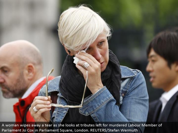 A lady wipes away a tear as she takes a gander at tributes left for killed Labor Member of Parliament Jo Cox in Parliament Square, London. REUTERS/Stefan Wermuth