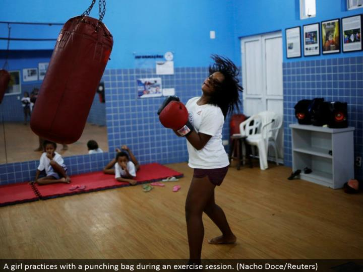 A young lady hones with a punching sack amid an activity session. (Nacho Doce/Reuters)