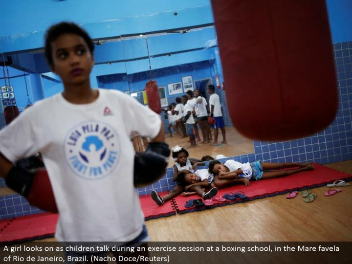 A young lady looks on as youngsters talk amid an activity session at a boxing school, in the Mare favela of Rio de Janeiro, Brazil. (Nacho Doce/Reuters)