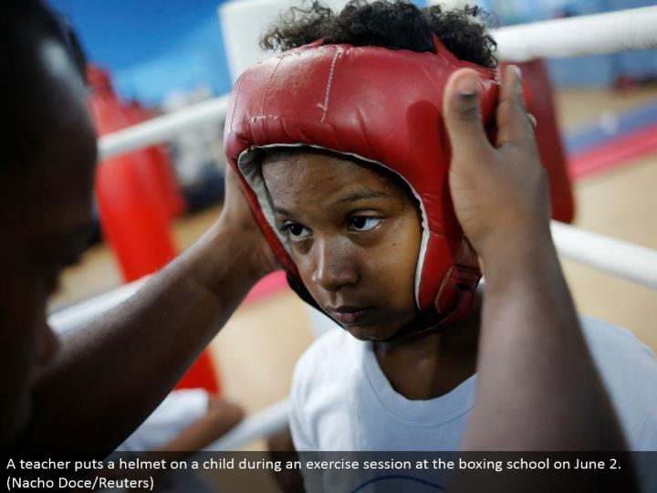 A educator puts a head protector on a tyke amid an activity session at the boxing school on June 2. (Nacho Doce/Reuters)