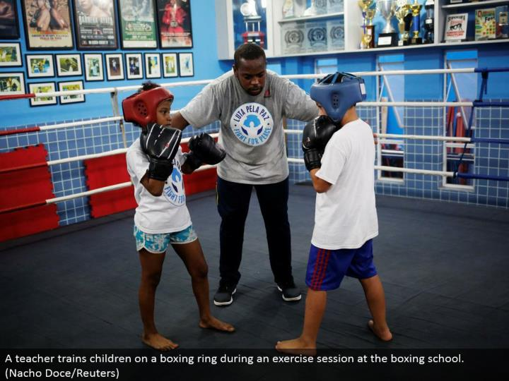 A instructor trains youngsters on a boxing ring amid an activity session at the boxing school. (Nacho Doce/Reuters)