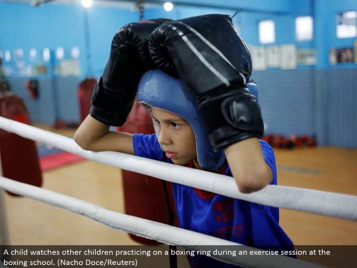 A youngster watches other kids honing on a boxing ring amid an activity session at the boxing school. (Nacho Doce/Reuters)