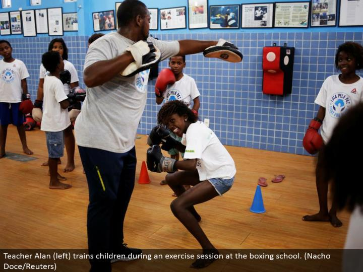 Teacher Alan (left) prepares kids amid an activity session at the boxing school. (Nacho Doce/Reuters)