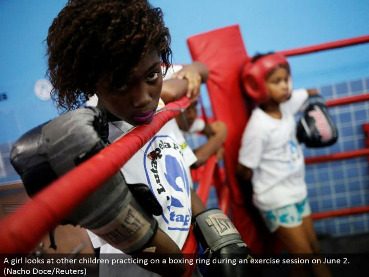 A young lady takes a gander at other kids honing on a boxing ring amid an activity session on June 2. (Nacho Doce/Reuters)