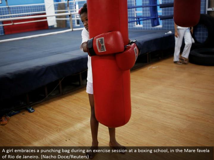 A young lady grasps a punching sack amid an activity session at a boxing school, in the Mare favela of Rio de Janeiro. (Nacho Doce/Reuters)