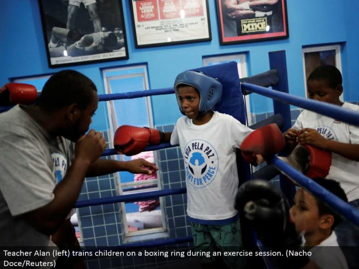 Teacher Alan (left) prepares youngsters on a boxing ring amid an activity session. (Nacho Doce/Reuters)