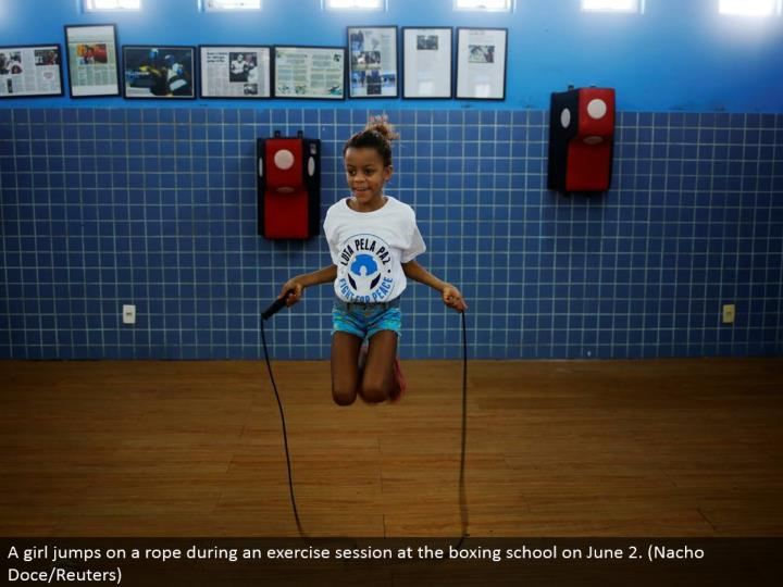 A young lady bounced on a rope amid an activity session at the boxing school on June 2. (Nacho Doce/Reuters)