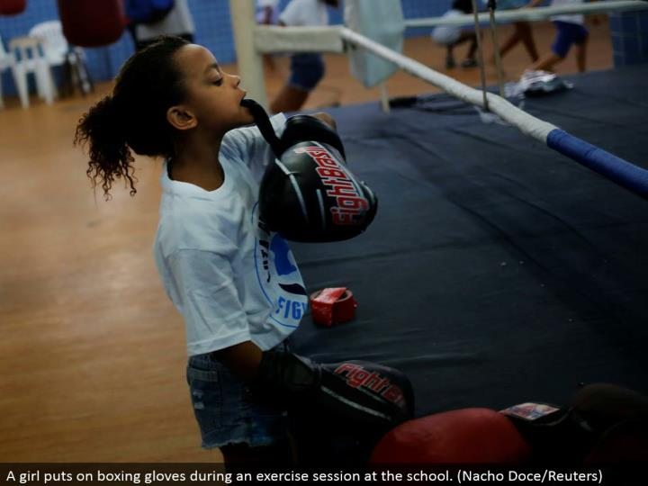 A young lady puts on boxing gloves amid an activity session at the school. (Nacho Doce/Reuters)
