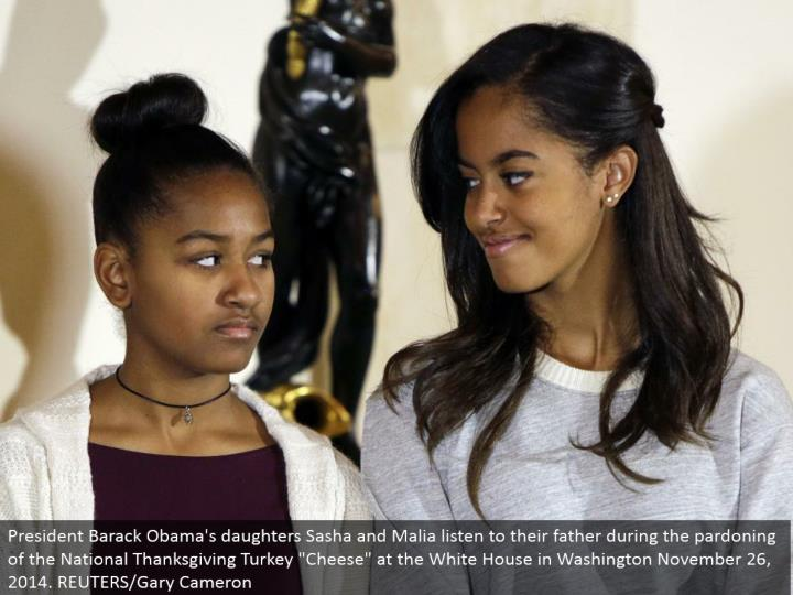 "President Barack Obama's little girls Sasha and Malia listen to their dad amid the acquitting of the National Thanksgiving Turkey ""Cheddar"" at the White House in Washington November 26, 2014. REUTERS/Gary Cameron"