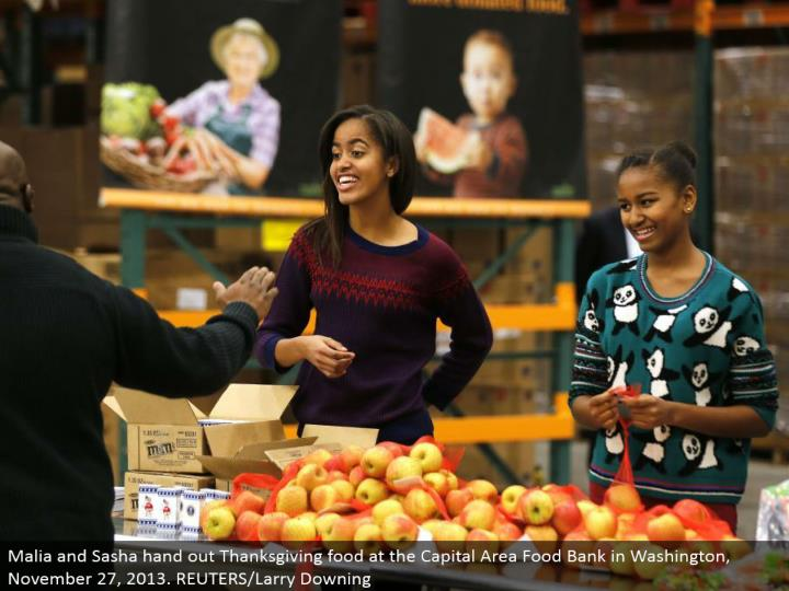Malia and Sasha hand out Thanksgiving sustenance at the Capital Area Food Bank in Washington, November 27, 2013. REUTERS/Larry Downing