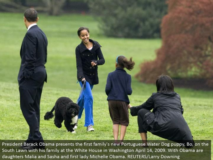 President Barack Obama presents the primary family's new Portuguese Water Dog puppy, Bo, on the South Lawn with his family at the White House in Washington April 14, 2009. With Obama are little girls Malia and Sasha and first woman Michelle Obama. REUTERS/Larry Downing