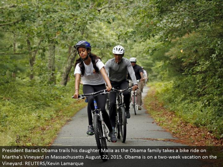 President Barack Obama trails his little girl Malia as the Obama family takes a bicycle ride on Martha's Vineyard in Massachusetts August 22, 2015. Obama is on a two-week get-away on the Vineyard. REUTERS/Kevin Lamarque
